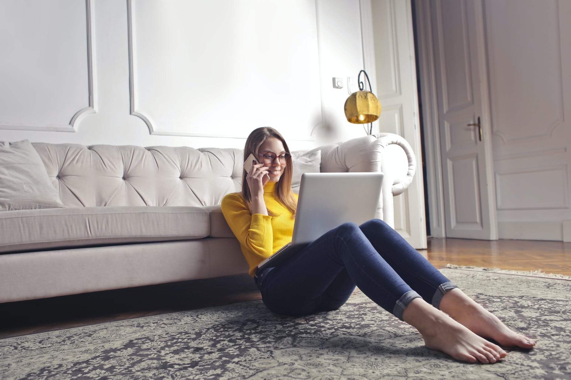 happy adult woman talking on phone and using laptop while chilling at home